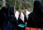 """Junge Studentinnen in der vorgeschriebenen Kleiderordnung """"hejab"""", schwarzer lager Mantel und Magna-e (Kaputze), essen Zuckerwatte in der Freizeit, Teheran, Iran 2004  © Ulla Kimmig"""
